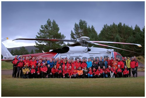 Some of the Scottish Mountain Rescue team with one of their helicopters.