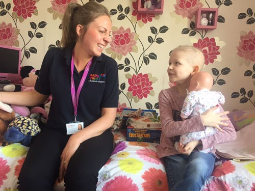 Rainbow trust volunteer with a child in her family home