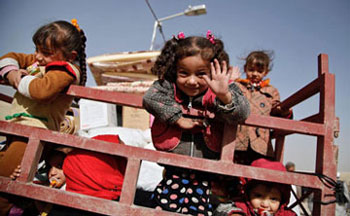 A child waves from the back of a truck as their family prepares to return home from Qayyarah Jad'ah camp.