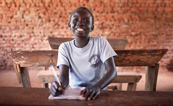 An unaccompanied child refugee from South Sudan, tries on uniform in a classroom in Imvepi.